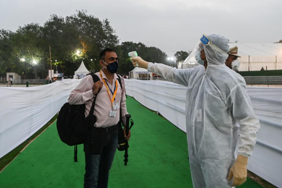 A security personnel wearing a Personal Protective Equipment (PPE) suit checks the body temperature of a photojournalist before the start of a ceremony to celebrate India's 74th Independence Day in New Delhi on August 15, 2020. (Photo by PRAKASH SINGH/AFP via Getty Images)