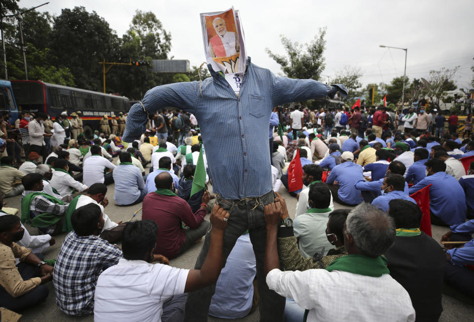 Protesting farmers hold an effigy of Indian prime minister Narendra Modi during a demonstration against new farming laws in Bangalore, India, on Dec. 9, 2020. Modi Friday held virtual talks with farmers from six states and asked them to explain how the government's agricultural policies have benefited them, a month after facing massive farmer protests that have rattled his administration. (AP Photo/Aijaz Rahi)