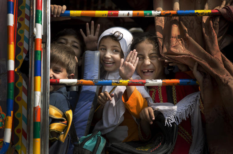 In this Friday, Oct. 4, 2013 photo, Pakistani children peek out of a bus as they leave school in Wajah Khiel, Swat Valley, Pakistan. One year after a Taliban bullet tried to silence Malala Yousufzai's demand for education, she has published a book and is a contender for the Nobel Peace Prize. But still the militants threaten to kill her should she dare return home to Pakistan, and the principal at her old school says that as Malala's fame has grown, so has fear in her classrooms. (AP Photo/Anja Niedringhaus)