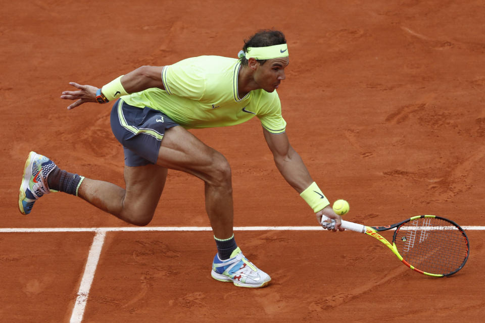 FILE - In this June 9, 2019, file photo, Spain's Rafael Nadal reaches for the ball as he plays Austria's Dominic Thiem during the men's final of the French Open tennis tournament at Roland Garros stadium in Paris. If the French Open were being held as scheduled right now, Nadal would have been seeking a 20th Grand Slam title to equal Roger Federers record for men. (AP Photo/Jean-Francois Badias, File)