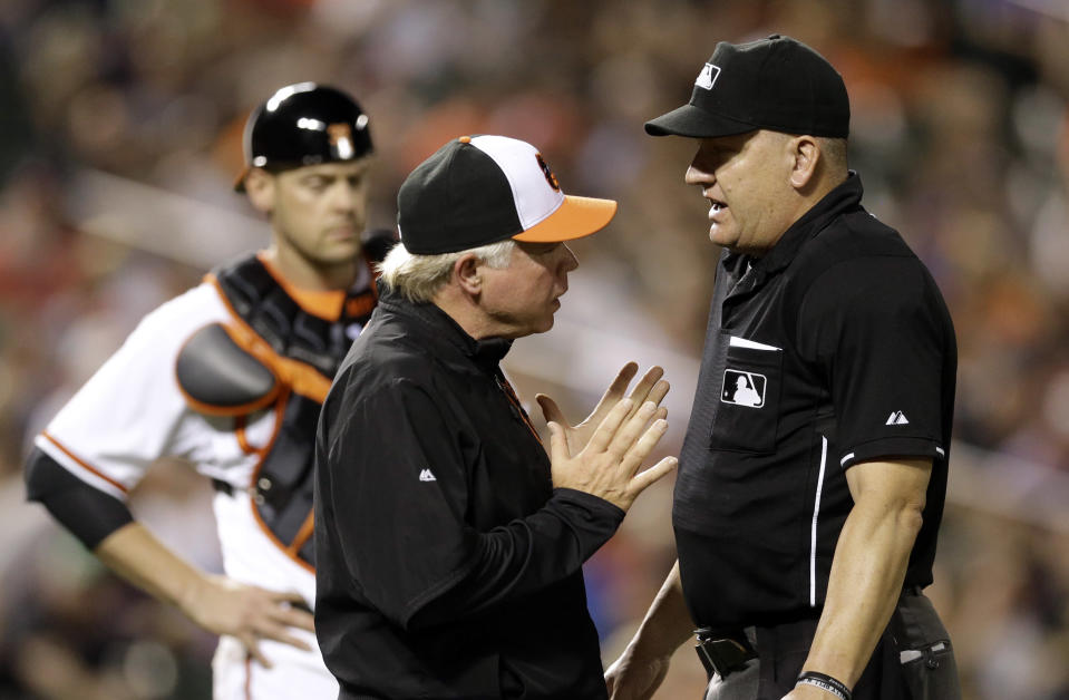 Baltimore Orioles manager Buck Showalter, left, speaks with home plate umpire Jeff Nelson before asking him to review a play in the seventh inning of a baseball game against the Boston Red Sox, Tuesday, June 9, 2015, in Baltimore. The play was reversed after Boston Red Sox's Xander Bogaerts was initially called safe at first on a single. Baltimore won 1-0. (AP Photo/Patrick Semansky)