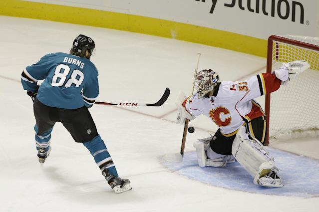 Calgary Flames goalie Karri Ramo, right, blocks a penalty shot by San Jose Sharks right wing Brent Burns during the first period of an NHL hockey game Saturday, Oct. 19, 2013, in San Jose, Calif. (AP Photo/Eric Risberg)
