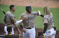 San Diego Padres' Mitch Moreland, center, is congratulated by Manny Machado, left, and Fernando Tatis Jr., right, after scoring during the eleventh inning of a baseball game against the Seattle Mariners Sunday, Sept. 20, 2020, in San Diego. (AP Photo/Denis Poroy)