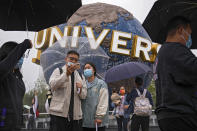 People wearing face masks to help protect themselves from the coronavirus pose for a selfie with an icon near the entrance to the Universal Studios Beijing in Beijing, Monday, Sept. 20, 2021. Thousands of people brave the rain visit to the newest location of the global brand of theme parks which officially opens on Monday. (AP Photo/Andy Wong)