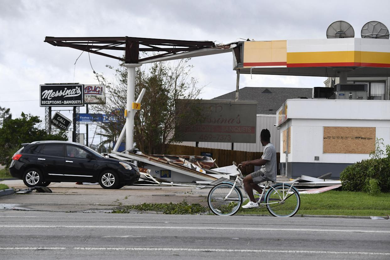A person on a bicycle passes a damaged gas station.