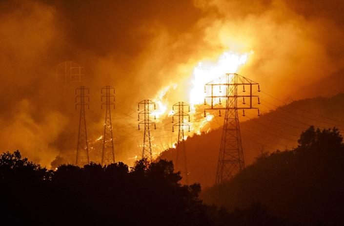 """Flames whip around utility power lines as winds drive towards town in Sycamore Canyon threatening structures in Montecito during the Thomas Fires, which authorities say was sparked by power lines. <span class=""""copyright"""">(Los Angeles Times)</span>"""