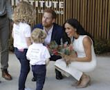 """<p>At the zoo where they met the koala, Harry and Meghan also met two children who presented them with native flowers at Taronga Zoo. <a href=""""https://www.cosmopolitan.com/uk/reports/g23854092/prince-harry-kids-photos/"""" rel=""""nofollow noopener"""" target=""""_blank"""" data-ylk=""""slk:As they often expertly do"""" class=""""link rapid-noclick-resp"""">As they often expertly do</a>, the couple bent down to speak to the kids on the same level.</p>"""
