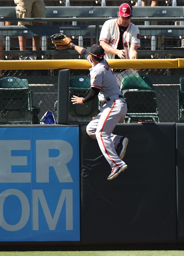 San Francisco Giants left fielder Gregor Blanco climbs the fence in a failed attempt to catch a three-run home run by Colorado Rockies' Nolan Arenado in the fifth inning of the Rockies' 9-2 victory in a baseball game in Denver on Wednesday, Sept. 3, 2014. (AP Photo/David Zalubowski)