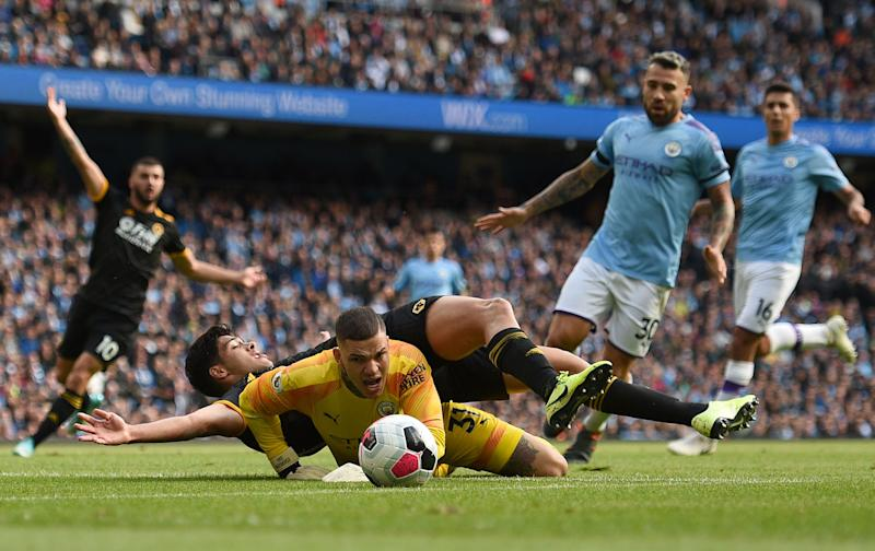 Wolverhampton Wanderers' Mexican striker Raul Jimenez lands on the back of Manchester City's Brazilian goalkeeper Ederson after the keeper made a save during the English Premier League football match between Manchester City and Wolverhampton Wanderers at the Etihad Stadium in Manchester, north west England, on October 6, 2019. (Photo by Oli SCARFF / AFP) / RESTRICTED TO EDITORIAL USE. No use with unauthorized audio, video, data, fixture lists, club/league logos or 'live' services. Online in-match use limited to 120 images. An additional 40 images may be used in extra time. No video emulation. Social media in-match use limited to 120 images. An additional 40 images may be used in extra time. No use in betting publications, games or single club/league/player publications. / (Photo by OLI SCARFF/AFP via Getty Images)