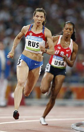 Sanya Richards of the U.S. (R) chases after Anastasia Kapachinskaya of Russia as they race toward the finish line of their women's 4 x 400m relay final of the athletics competition in the National Stadium at the Beijing 2008 Olympic Games August 23, 2008 (file photo).     REUTERS/Jerry Lampen