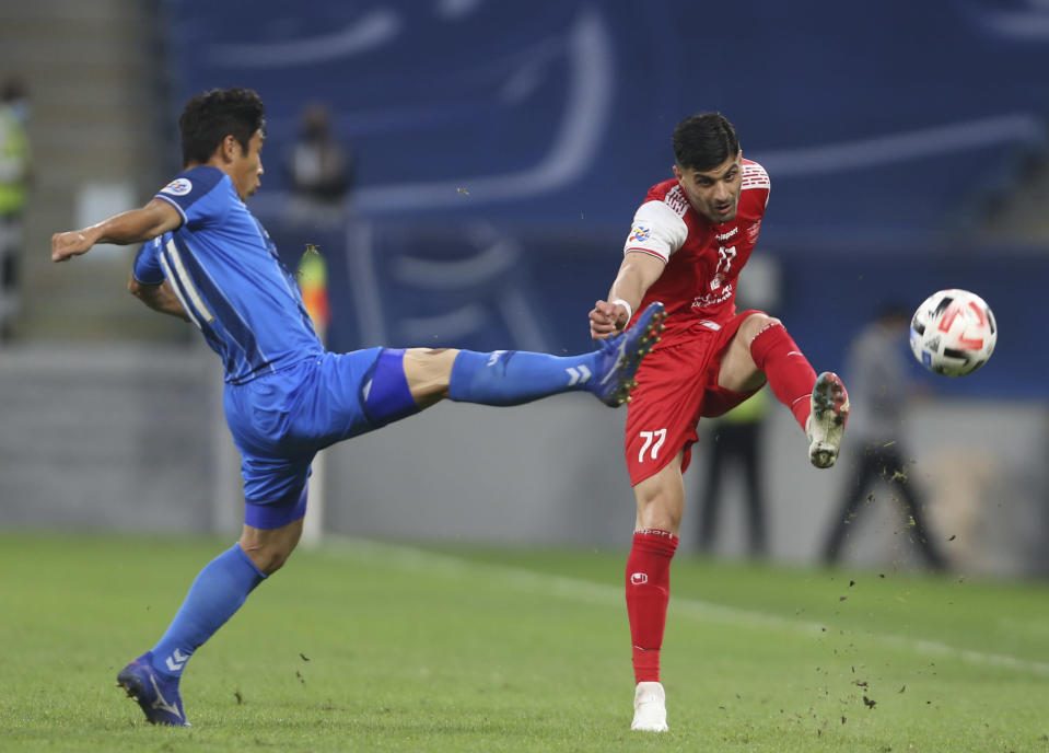 Ulsan Hyundai's Lee Keun-Ho, left, and Saeid Aghaei of Persepolis fight for the ball during the AFC Champions League final match in Al Wakrah, Qatar, Saturday, Dec. 19, 2020. (AP Photo/Hussein Sayed)