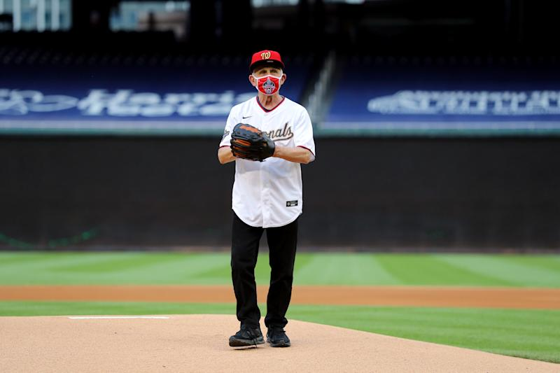 Dr. Anthony Fauci stands on a baseball mound wearing a mask.