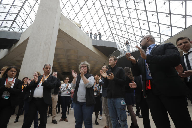 Le Louvre museum employees applaud to pay tribute to the architect of its giant glass pyramid, I.M. Pei, Friday, May 17, 2019 in Paris. Pei died earlier this week at the age of 102. (AP Photo/Michel Euler)