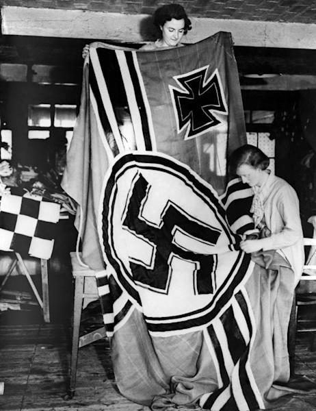 A picture dated 1936 shows German female workers making Third Reich flags with Nazi symbols including the Iron Cross and the Swastika designed by Hitler himself