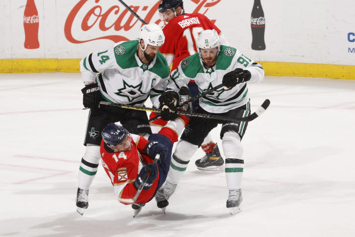 Dallas Stars center Tyler Seguin (91) and left-wing Jamie Benn (14) check Florida Panthers left wing Grigori Denisenko (14) during the third period of an NHL hockey game, Monday, May 3, 2021, in Sunrise, Fla. (AP Photo/Joel Auerbach)
