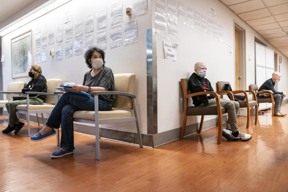 Elissa Montanti, founder and director at The Global Medical Relief Fund, center left, handles paperwork for Baraka Cosmas, 12, and three other children living with albinism, before they receive COVID-19 vaccinations at Richmond University Medical Center, Friday, June 4, 2021, in the Staten Island borough of New York. The pandemic put a hold on international travel and on the services Montanti has facilitated for the more than 450 kids who have passed through her care. As restrictions have begun lifting across the country, the Staten Island woman is bringing her charity back to life. (AP Photo/John Minchillo)