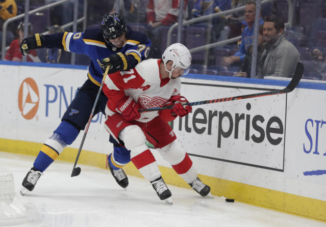St. Louis Blues' Oskar Sundqvist (70) battles Detroit Red Wings' Dylan Larkin (71) for the puck in the first period of an NHL hockey game, Thursday, March 21, 2019, in St. Louis. (AP Photo/Tom Gannam)
