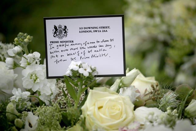 A wreath sent by prime Minister Boris Johnson among the flowers outside St George's Chapel at Windsor Castle, Berkshire
