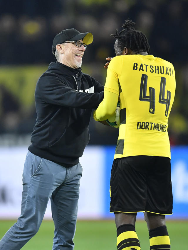 Dortmund's match winner Michy Batshuayi is pushed by Dortmund's head coach Peter Stoeger after the German Bundesliga soccer match between Borussia Dortmund and Eintracht Frankfurt in Dortmund, Germany, Sunday, March 11, 2018. Dortmund defeated Frankfurt in a dramatic 3-2. (AP Photo/Martin Meissner)