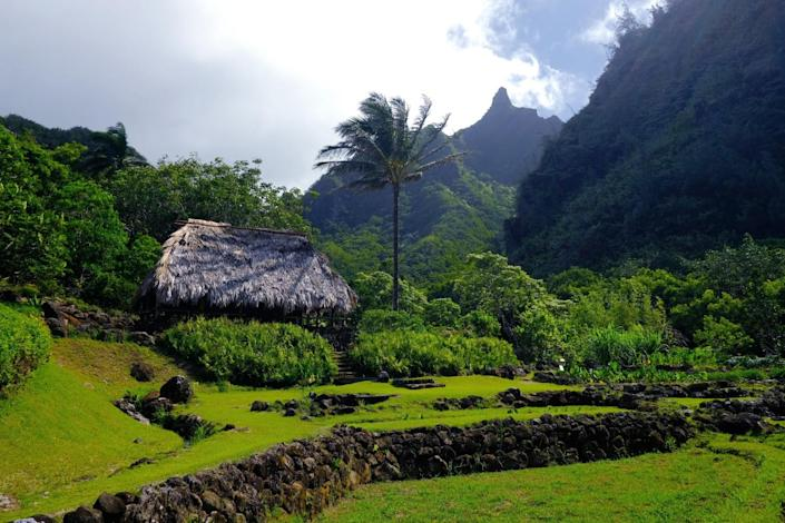 The brown roof of a grass hut sits amid abundant vegetation and green mountainsides.