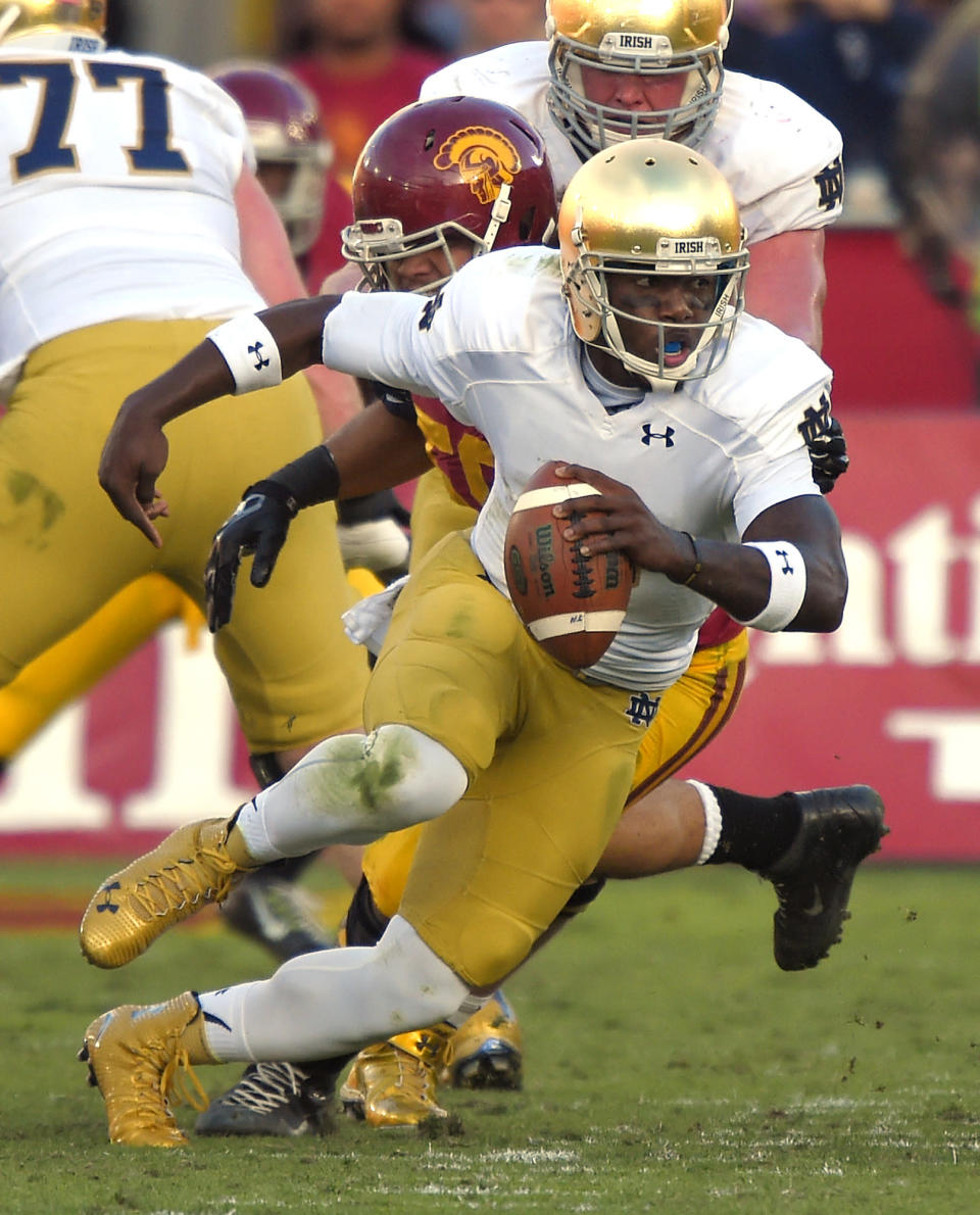 Notre Dame quarterback Malik Zaire, right, is sacked by Southern California linebacker J.R. Tavai during the second half of an NCAA college football game, Saturday, Nov. 29, 2014, in Los Angeles. Southern California won 49-14. (AP Photo/Mark J. Terrill)