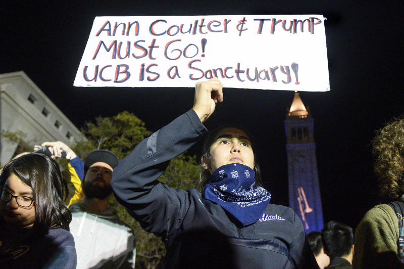 """University of California, Berkeley student Magaly Mercado holds a protest sign as attendees leave a speech by conservative commentator Ann Coulter on Wednesday, Nov. 20, 2019, in Berkeley, Calif. Hundreds of demonstrators gathered on campus as Coulter delivered a talk titled """"Adios, America!"""" (AP Photo/Noah Berger)"""