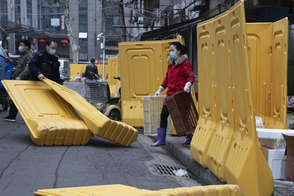 FILE - In this April 5, 2020, file photo, a city worker removes barriers used to seal off a community as the city of Wuhan slowly loosen up ahead of a lifting of the two month long lockdown in central China's Hubei province. One year after Wuhan's lockdown to curb the coronavirus, the Chinese city has long since sprung back to life. (AP Photo/Ng Han Guan, File)