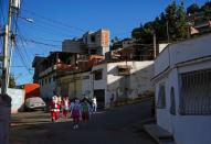 Man dressed up as Santa Claus and others walk in a low-income neighbourhood in Guarenas
