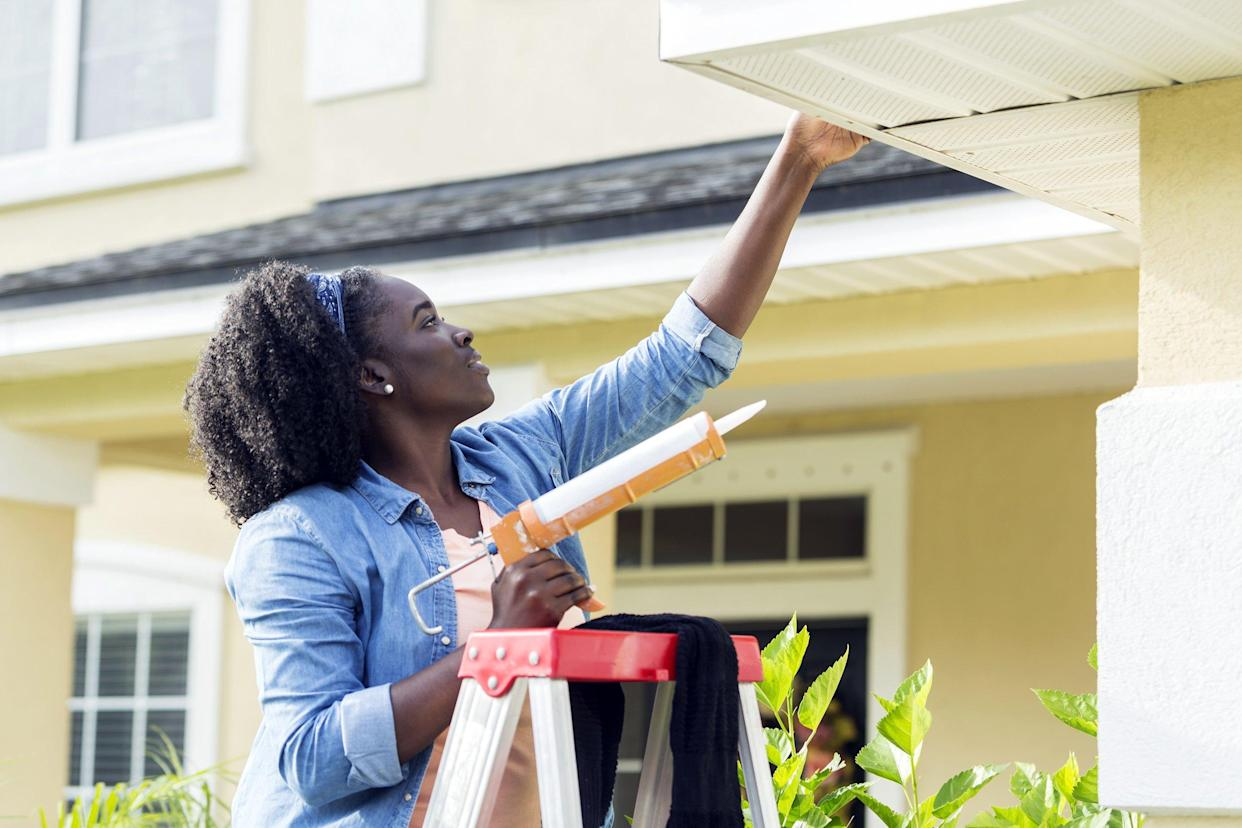 Woman on a ladder doing house repairs outside