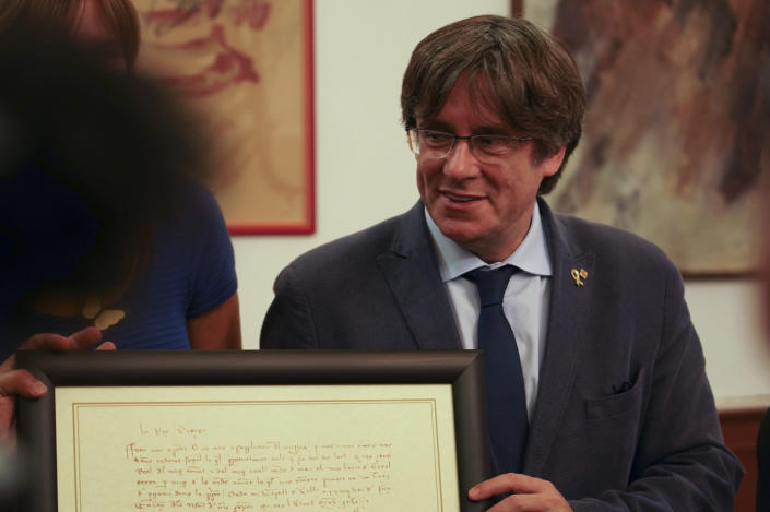 Catalan separatist leader Carles Puigdemont, exchanges gifts with Mayor of Alghero Mario Conoci, left, in Alghero, Sardinia, Italy, Saturday, Sept. 25, 2021. Puigdemont was visiting the city hall after he took a leisurely walk in the Sardinian city, waving to supporters, a day after a judge freed him from jail pending a hearing on his extradition to Spain, where the political firebrand is wanted for sedition. (AP Photo/Andrea Rosa)