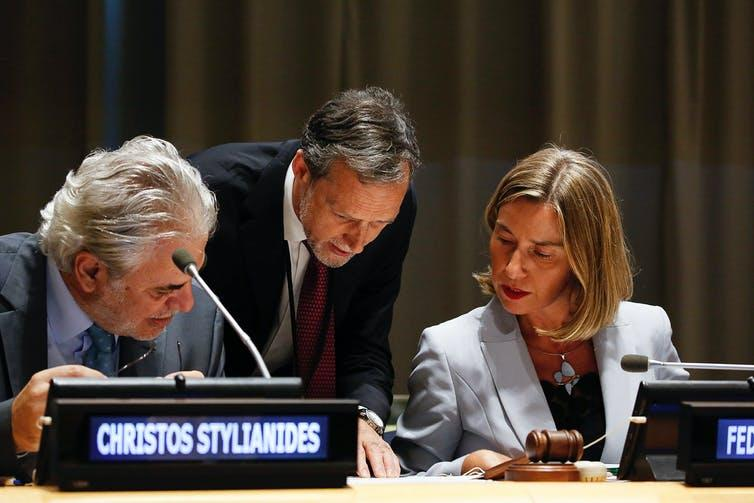 Diplomats discussing document at UN general assembly.