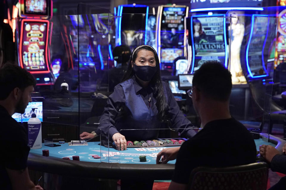 FILE - In this June 4, 2020 file photo, people play blackjack at the reopening of the Bellagio hotel and casino in Las Vegas. Some Las Vegas casinos are updating their smoking policies to limit the practice, which causes people to remove the protective face masks that they're required to wear inside. (AP Photo/John Locher, File)