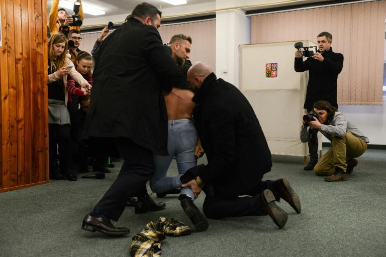 Security staff of Czech President Milos Zeman (not in picture) detained a woman being member of the Femen organisation after she attacked the President on January 12, 2018 at the polling station in Prague