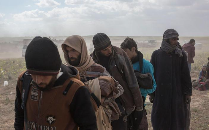 Suspected Isil militants led away to be questioned by US-led coalition forces after surrendering, near Baghuz, in eastern Syria - Sam Tarling for The Telegraph