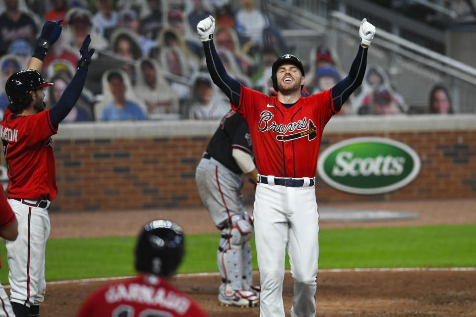"""FILE - In this Sept. 4, 2020, file photo, Atlanta Braves' Freddie Freeman celebrates as he crosses home plate after hitting a grand slam to center field during the fourth inning of the second baseball game of the team's doubleheader against the Washington Nationals in Atlanta. Freeman easily won the NL MVP award Thursday, Nov. 12, topping off a trying year that saw him become so ill with COVID-19 he prayed """"please don't take me."""" (AP Photo/John Amis, File)"""