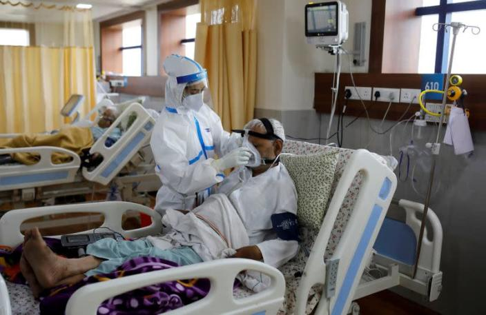 FILE PHOTO: A medical worker takes care of a patient suffering from the coronavirus disease (COVID-19), at a hospital in Noida