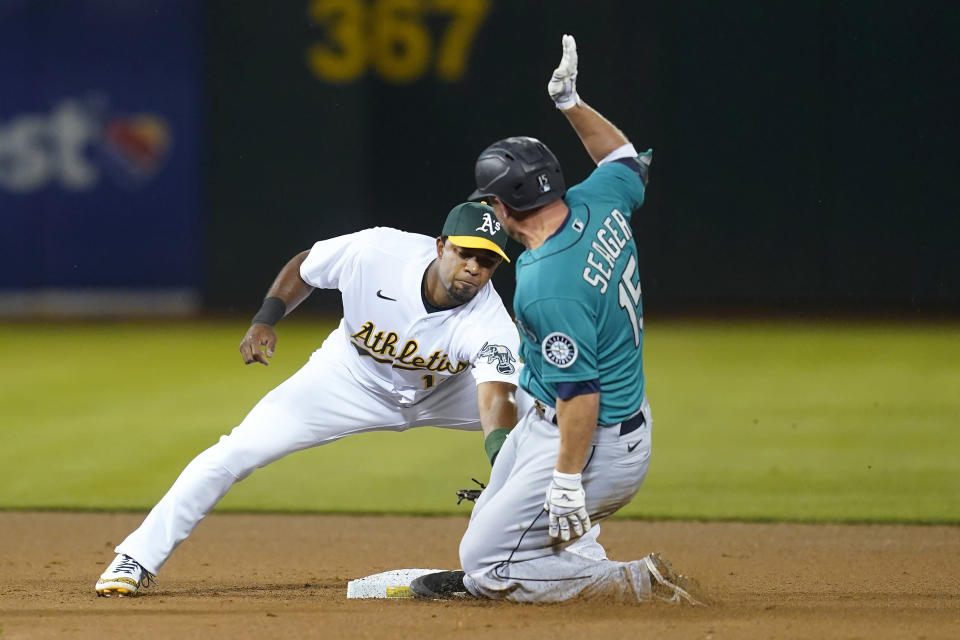 Seattle Mariners' Kyle Seager, right, is tagged out by Oakland Athletics shortstop Elvis Andrus trying to advance to second base on an RBI-single during the fifth inning of a baseball game in Oakland, Calif., Monday, Sept. 20, 2021. (AP Photo/Jeff Chiu)