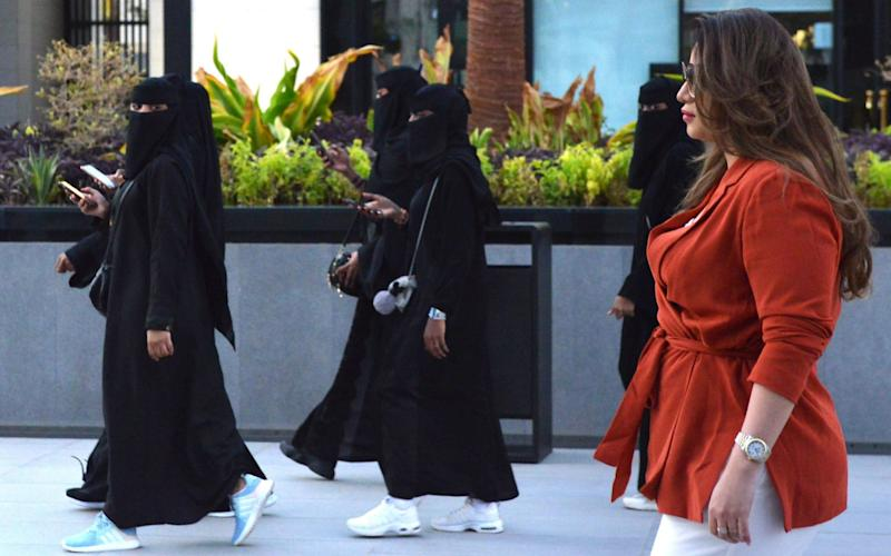 Saudi human resources professional Mashael al-Jaloud, 33, walks in western clothes past women wearing niqab, an Islamic dress-code for women, at a commercial area in the Saudi capital Riyadh - AFP