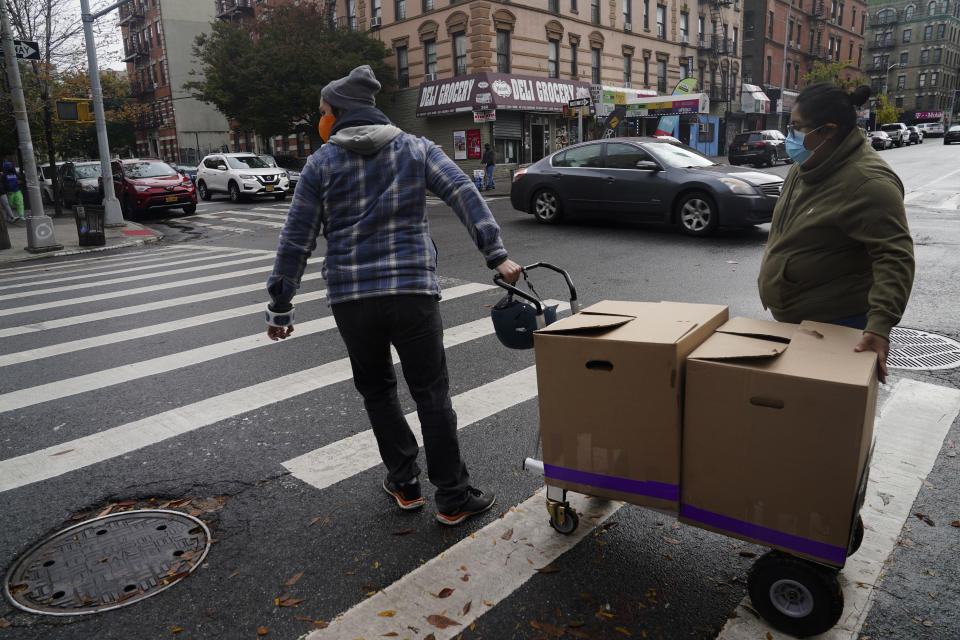 Yahaira Saavedra, right, co-owner of the Mexican restaurant La Morada, and volunteer Dan Zimberg, left, cross a street pushing a trolley load of boxed meals prepared at the South Bronx restaurant, Wednesday Oct. 28, 2020, in New York. After a fund raising campaign during the coronavirus pandemic, Saavedra and her parents transformed the restaurant into a soup kitchen, serving 650 meals daily. (AP Photo/Bebeto Matthews)
