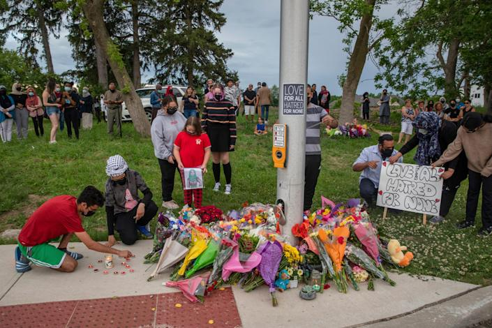 People attend a memorial at the location where a family of five was hit by a driver, in London, Ontario, Monday, June 7, 2021. Four of the members of the family died and one is in critical condition. A 20-year-old male has been charged with four counts of first degree murder and count of attempted murder in connection with the crime.