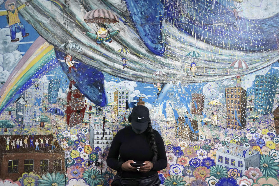 A protester stands in front of wall painting before a solidarity rally for the death of George Floyd in Tokyo Sunday, June 14, 2020. Floyd died after being restrained by Minneapolis police officers on May 25. (AP Photo/Eugene Hoshiko)