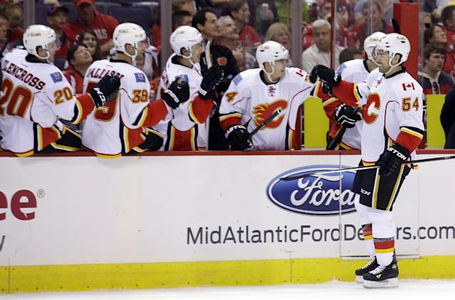 Calgary Flames right wing David Jones (54) celebrates his goal with teammates in the first period of an NHL hockey game against the Washington Capitals, Thursday, Oct. 3, 2013, in Washington. (AP Photo/Alex Brandon)