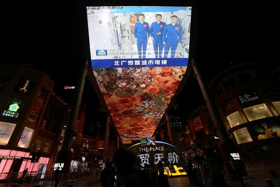 A giant screen shows a news broadcast of the astronauts of the Shenzhou-12 mission inside the core module Tianhe of the Chinese space station, before returning to Earth (REUTERS)