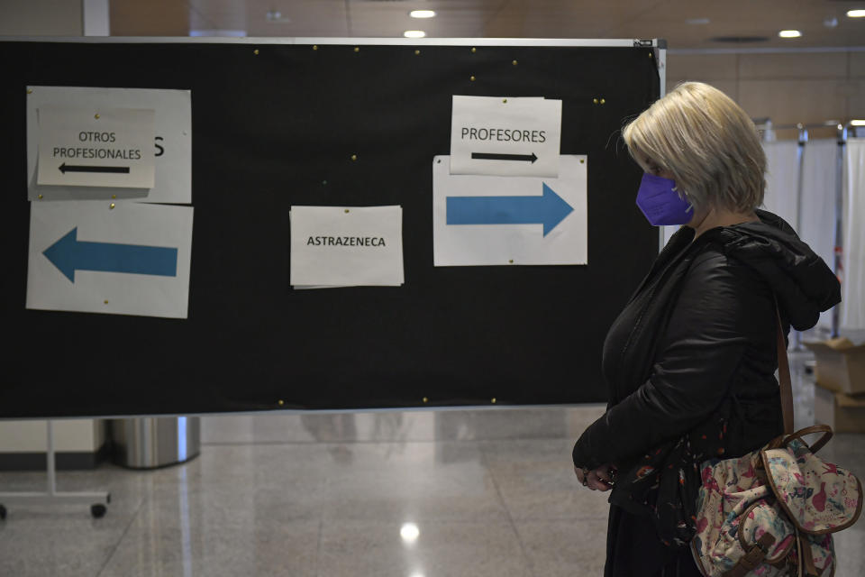 A woman waits close to an information board showing the use of the AstreZeneca COVID-19 vaccination at San Pedro Hospital, in Logrono, northern Spain, Wednesday, March 24. 2021. Spain resumed the use of the AstraZeneca vaccine on Wednesday. (AP Photo/Alvaro Barrientos)