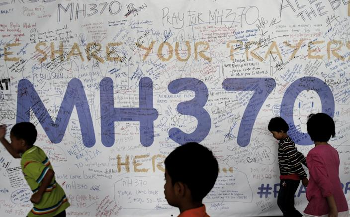 Children run past dedication messages and well wishes displayed for passengers and others involved with the missing Malaysia Airlines jetliner MH370 on the walls of the Kuala Lumpur International Airport, Thursday, March 13, 2014, in Sepang, Malaysia. Planes sent Thursday to check the spot where Chinese satellite images showed possible debris from the missing Malaysian jetliner found nothing, Malaysia's civil aviation chief said, deflating the latest lead in the six-day hunt. The hunt for the missing Malaysia Airlines flight 370 has been punctuated by false leads since it disappeared with 239 people aboard about an hour after leaving Kuala Lumpur for Beijing early Saturday. (AP Photo/Wong Maye-E)