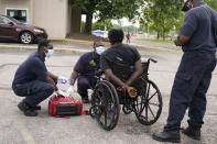 Paramedics help a man in distress in a parking lot in St. Louis on Saturday, May 22, 2021. He was found passed out in the middle of a busy parking lot. In the city of St. Louis, deaths among Black people increased last year at three times the rate of whites, skyrocketing more than 33% in a year. (AP Photo/Brynn Anderson)