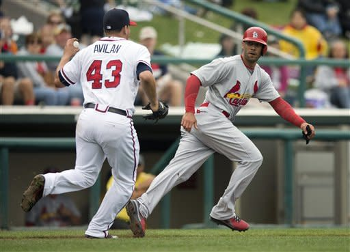 St. Louis Cardinals' Justin Christian, right, is chased by Atlanta Braves pitcher Luis Avilan after being caught in a run-down during the seventh inning of an exhibition spring training baseball game on Tuesday, March 12, 2013, in Kissimmee, Fla. (AP Photo/Evan Vucci)