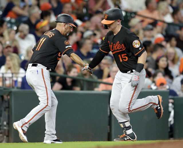 Baltimore Orioles third base coach Jose David Flores (11) low-fives Chance Sisco (15), who rounds the bases after his home run against the Houston Astros during the third inning of a baseball game Friday, June 7, 2019, in Houston. (AP Photo/Michael Wyke)