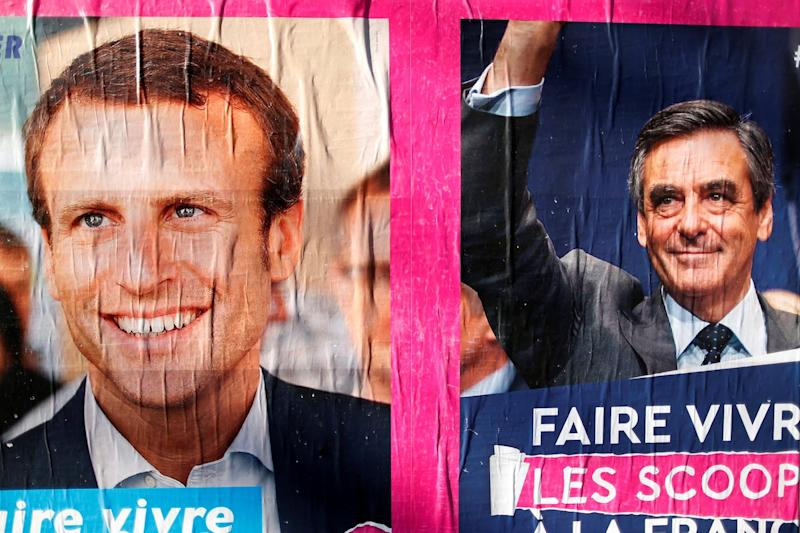 Campaign posters for 2017 presidential election candidates Francois Fillon (R) of the Republicans political party and Emmanuel Macron (L), head of the political movement En Marche !, or Onwards !, are seen in Paris, France, April 3, 2017.