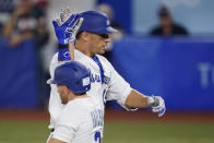 Israel's Danny Valencia, top, celebrate with Blake Gailen after hitting a home run in the fourth inning of a baseball game against the United States at the 2020 Summer Olympics, Friday, July 30, 2021, in Yokohama, Japan. (AP Photo/Sue Ogrocki)